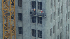Time lapse of construction workers and window cleaners on a tall building Stock Footage