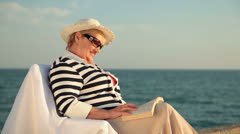 Senior lady relaxing on the seacoast Stock Footage