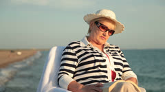 Senior lady relaxing on  the seacoast at sunset Stock Footage