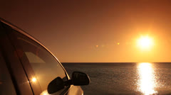Car on the summer beach at sunset - stock footage