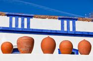 Stock Photo of clay pots stand on white pottery wall in portugal
