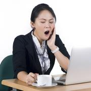 young business woman yawning at her desk with a cup of coffee - stock photo