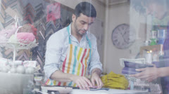 Store assistant takes a payment from a customer in his shop Stock Footage