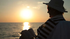 Senior lady silhouette by the sea at sunset Stock Footage