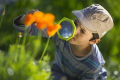 enfant observant la nature avec une loupe - stock photo