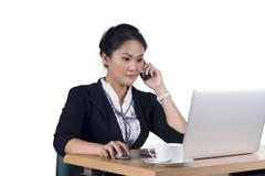 Portrait of business woman speaking on mobile phone while using laptop in off Stock Photos