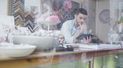Happy friendly store assistant serves a customer in his shop - stock footage