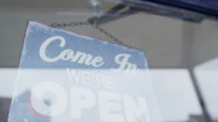 'Open' sign is turned to 'Closed' in a storefront window - stock footage