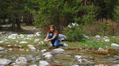 Happy, cheerful girl squirting water from the creek and laughs Stock Footage