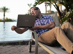 Man video chat on laptop while sitting by the swimming pool NTSC - stock footage
