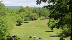 View of a golf course fairway in mountains with carts Stock Footage