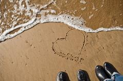 heart drawn with fingers on a beach just before a wave delete it - stock photo