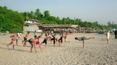 GOA, INDIA - MARCH 2013: Group of holidaymakers practicing yoga on sandy beach Stock Footage