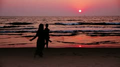 Silhouette of woman dancing at sunset on sea shore - stock footage
