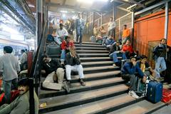 travellers waiting at delhi train station - stock photo