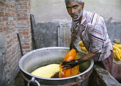 Stock Photo of man dyeing textile in india