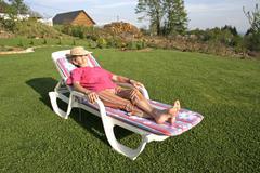 Woman pensioner enjoying her free time in garden Stock Photos
