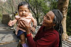gurung grand mother with grandchild, annapurna, nepal - stock photo