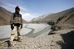 hiker standing in front of river valley in lower mustang, annapurna, nepal - stock photo