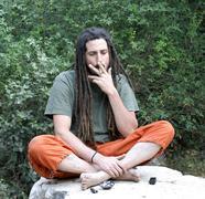 Hippy preparing, rolling and smoking marijuana joint : photos series Stock Photos