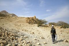 man walking in desert landscape in the dead sea region - stock photo
