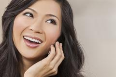 beautiful asian chinese woman talking on cell phone - stock photo