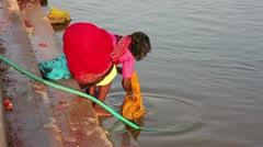HAMPI, KARNATAKA, INDIA - APRIL 2013: Local women doing laundry in river Stock Footage
