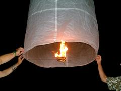 Fire lanterns taking off on the beach in thailand. Stock Photos