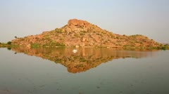 Rocky hill reflecting in water Stock Footage