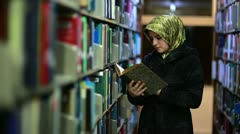 Female student wandering between shelves, searching for books Stock Footage