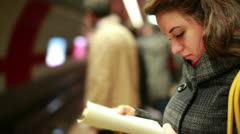 Woman reading book while waiting metro at station Stock Footage