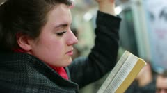 Woman reading book inside metro during her journey Stock Footage