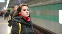 Metro coming to the station, young woman goes to train Stock Footage