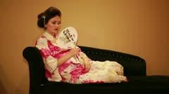 Japanese geisha on orange background fan herself Stock Footage
