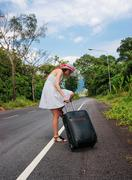 young girl walking down the road with a suitcase - stock photo