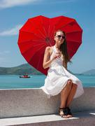 young girl with a red umbrella sits on the waterfront and looks at the sea - stock photo