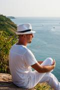 Stock Photo of a young man sitting on a rock and looking at the sunset of phuket