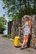 young girl standing on the road with a yellow suitcase - stock photo