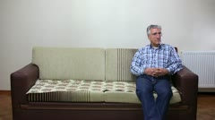 Senior couple talking while sitting on sofa Stock Footage