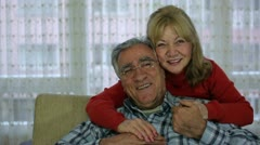 Senior couple laughing and talking while watching TV Stock Footage