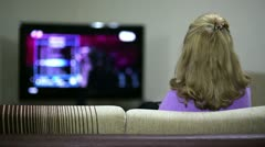 Woman watching TV show while sitting on sofa in her living room Stock Footage