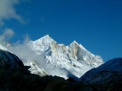 pristine view over mount bhagarathi, over 7700m high, few clouds floating abo - stock photo