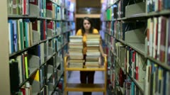 Stock Video Footage of Distressed female student wandering between shelves, searching for books