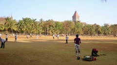 MUMBAI, INDIA - MARCH 2013: Group of people playing cricket in local park Stock Footage