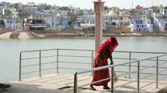 Woman swiping jetty, Pushkar cityscape in background Stock Footage
