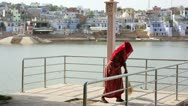 Stock Video Footage of Woman swiping jetty, Pushkar cityscape in background