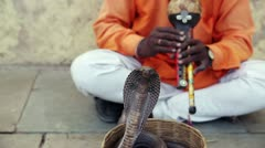 Cobra enchanter sitting in the street charming his snake Stock Footage