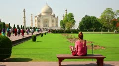 Caucasian woman sitting on bench and looking to Taj Mahal Stock Footage