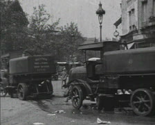 PARIS, FRANCE - 1920's: cleaning vehicles clean city street at crossing Stock Footage