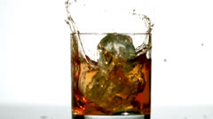 Ice cube falling in whiskey tumbler Stock Footage